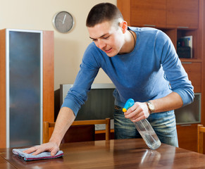 Smiling man dusting  table with rag and cleanser