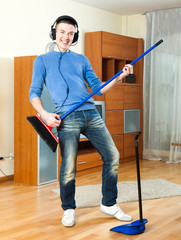 Cheerful hansome man  with dustpan and brush