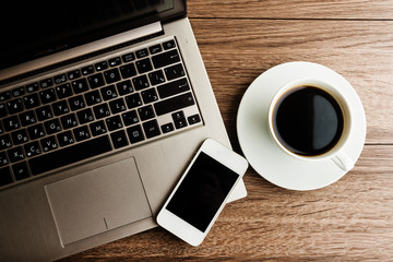 open laptop with phone and cup of coffee