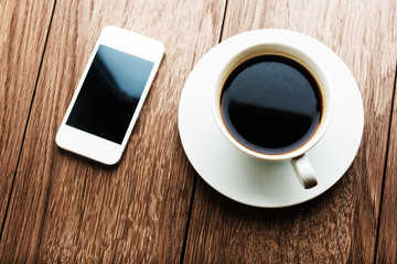 smart phone and coffee cup on wooden background.