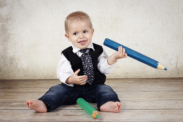 Little baby with tie holding big crayon