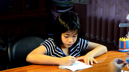 Young girl writing homework.
