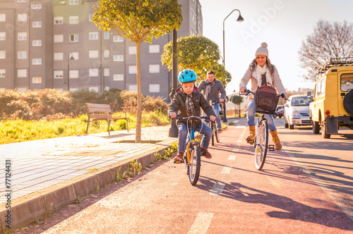 Family with child riding bicycles in the city - 77124431