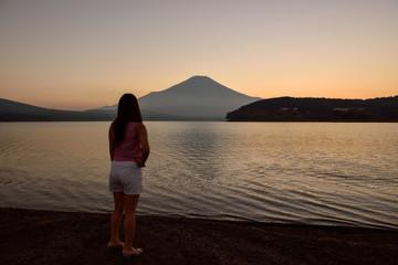 夕暮れの富士山を見てる女性