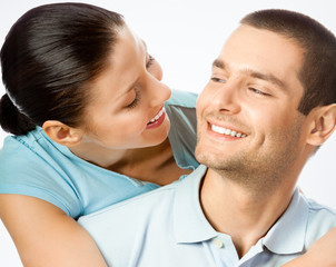 Cheerful amorous young couple, on grey