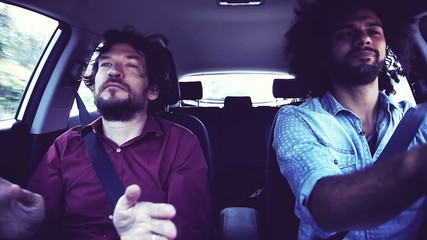Two funky cool hipster men driving car dancing retro style