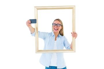 Blonde woman taking a selfie through a frame