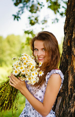 The beautiful young sexy girl with flowers in the field