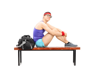 Pensive young sportsman sitting on a bench