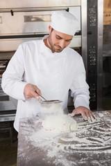 Focused baker sieving flour on the dough
