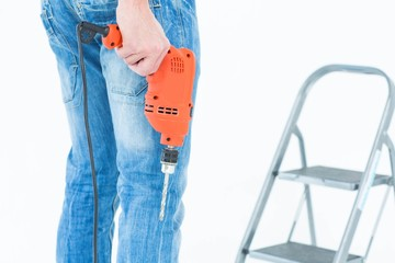 Worker holding drill in front of step ladder