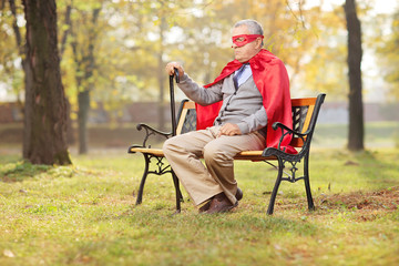 Sad senior in superhero outfit sitting in park