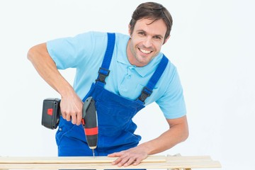 Carpenter using drill machine on wood
