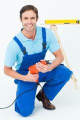 Happy carpenter holding drill machine