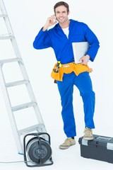 Electrician with leg on tool box using mobile phone