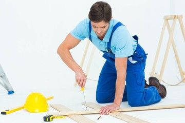 Repairman fixing screw on plank