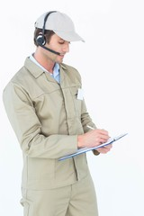 Delivery man using headphones while writing on clipboard