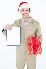 Delivery man in Santa hat holding clipboard and gift