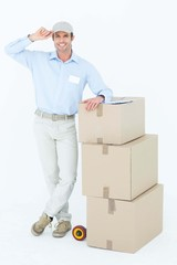 Happy delivery man leaning on stacked cardboard boxes