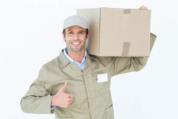 Delivery man showing thumbs up while carrying cardboard box