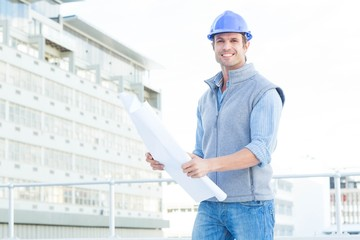 Happy male architect holding blueprint