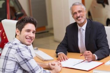 Smiling businessman and customer looking at camera