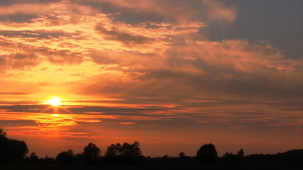 Sunset over a field in autumn. Time lapse.