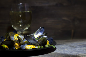 Mussels with glass of white wine and thyme in the dark