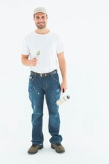 Happy man holding paint roller and paintbrush