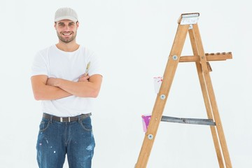 Happy man holding paint roller while standing by ladder