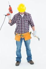 Male repairman holding drill machine and hammer