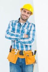 Happy repairman standing arms crossed
