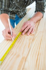 Carpenter marking with tape measure on wooden plank