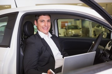 Smiling businessman using laptop in his car