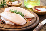 Raw chicken breast with fresh rosemary sprig and spices
