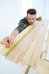 Worker using measure tape to mark on wooden plank