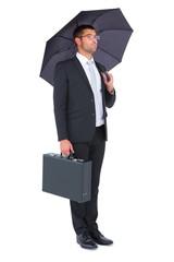 Businessman sheltering under bllack umbrella