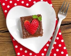 Creamy chocolate cake on heart shaped plate