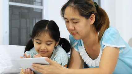 Little Asian mother and daughter using tablet on the bed