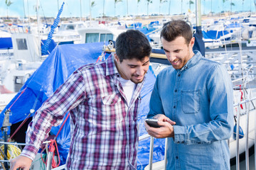 Two friends looking at mobile at the marina