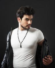 Man posing in black leather jacket, studio shot