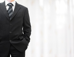 businessman in black suit with hand in pocket with blurred backg