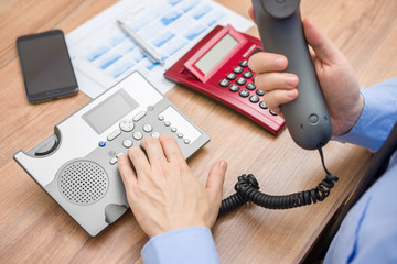 Occupied businessman with report  is calling client for explanat