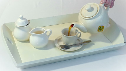 Pour tea into a cup on a tray