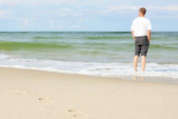 beach man standing water back view shallow dof footprints sand