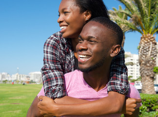 Happy young man carrying girlfriend on back