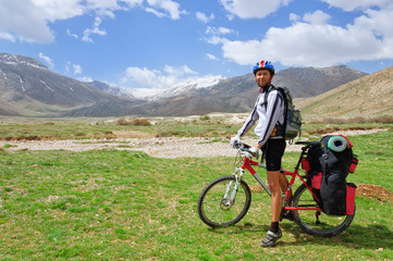 Cyclist with a large backpack standing on the  Turkish mountains