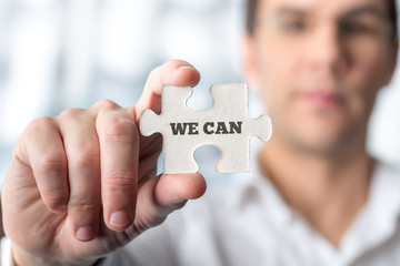 Businessman holding puzzle piece with We can text