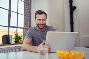 junger mann arbeitet zu hause am laptop