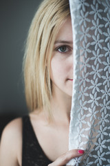blonde woman hiding behind the curtain